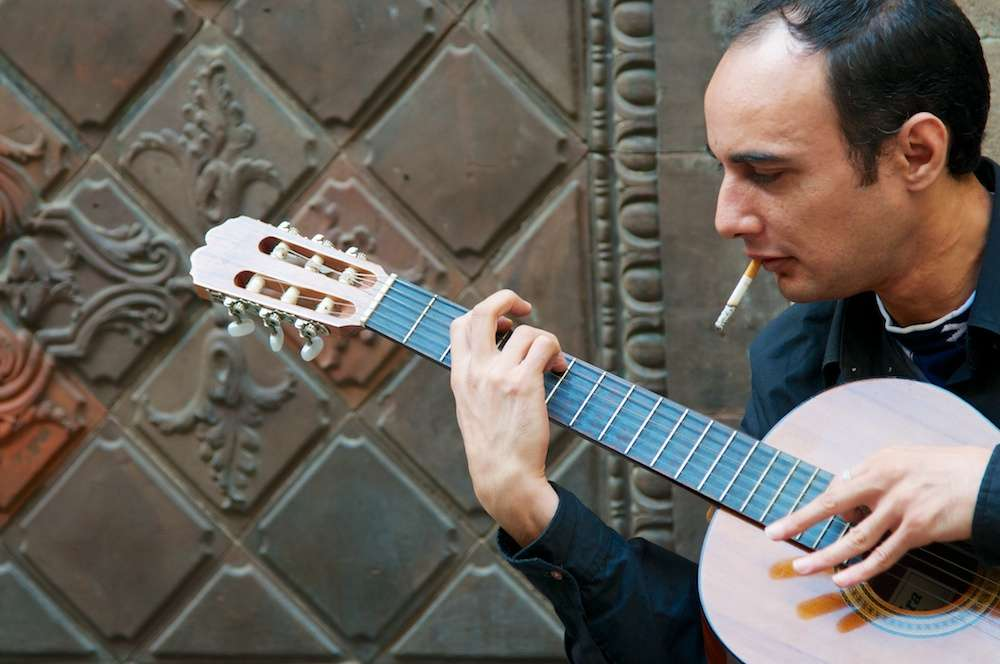 Flamenco guitarist with cigarette in his mouth in Barcelona, Spain by Ralph Velasco