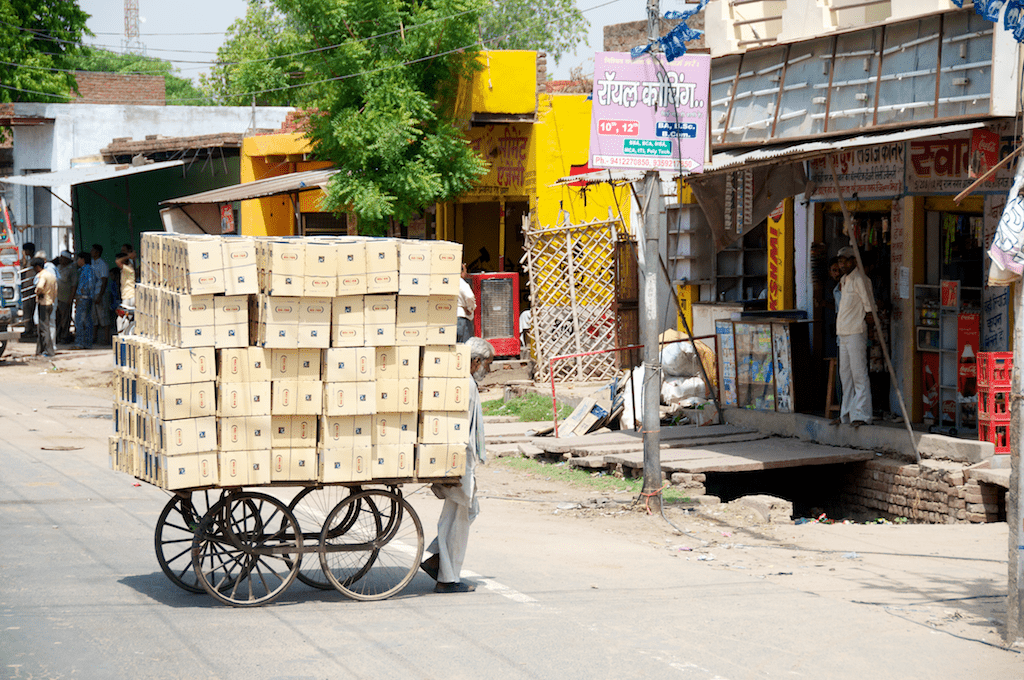 Box vendor crossing street in Agra, India by Ralph Velasco