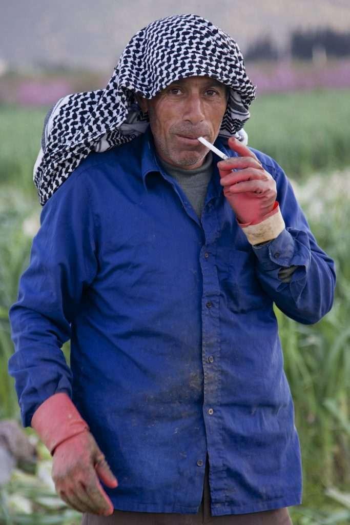 Man smoking cigarette in leek field near Kusadasi, Turkey by Ralph Velasco