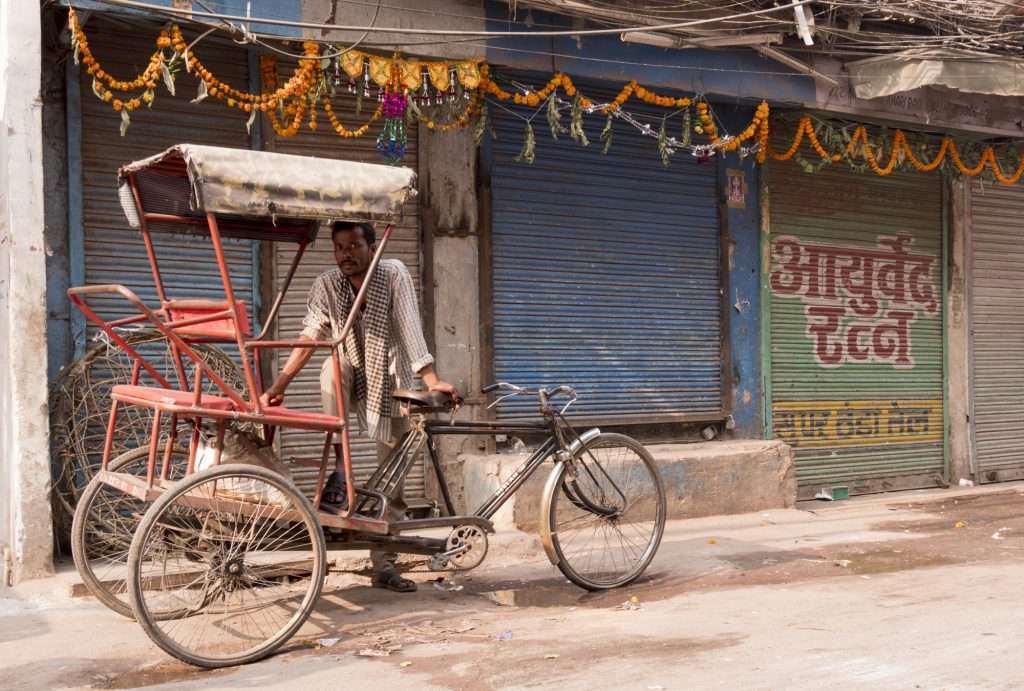 Man in spice market with rickshaw and marigolds hanging in Delhi, India by Ralph Velasco