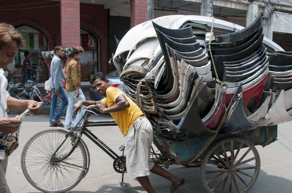Man with rickshaw stacked with car part in Delhi, India by Ralph Velasco