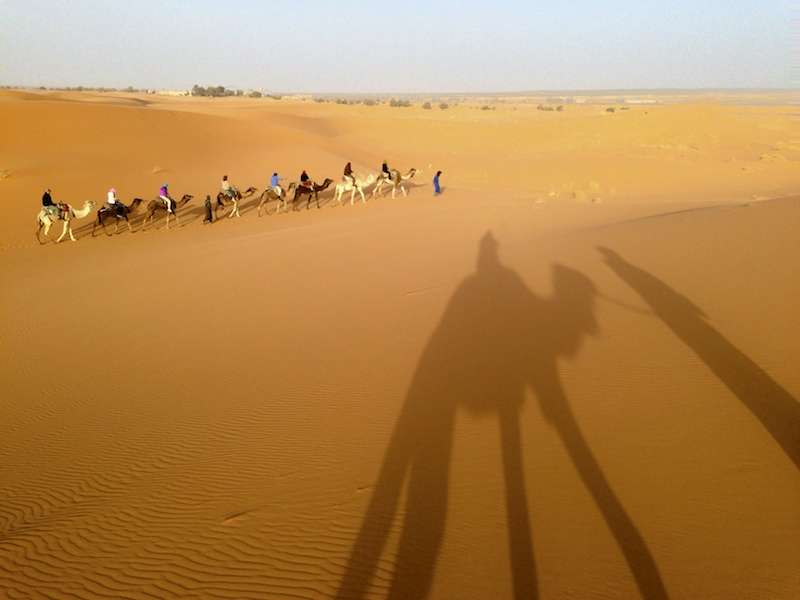 Shadow with group in the distance in the Sahara desert near Merzouga, Morocco