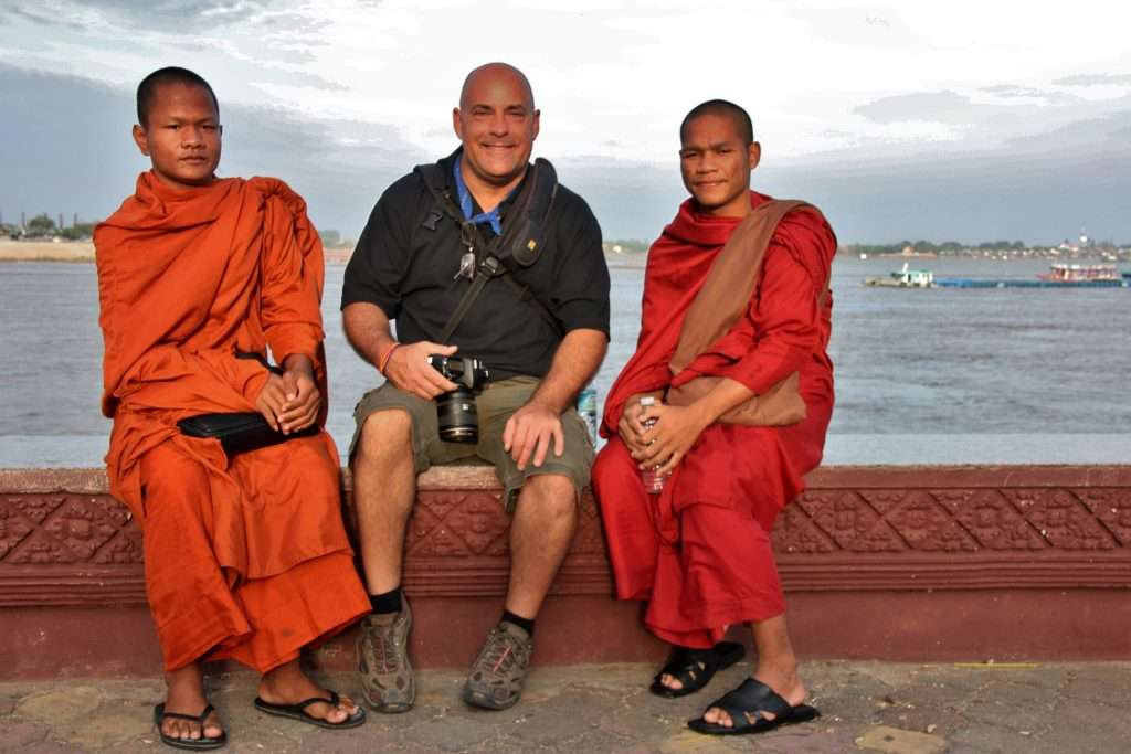 Ralph Velasco with young monks on riverfront in Phnom Penh, Cambodia by Carol Lloyd