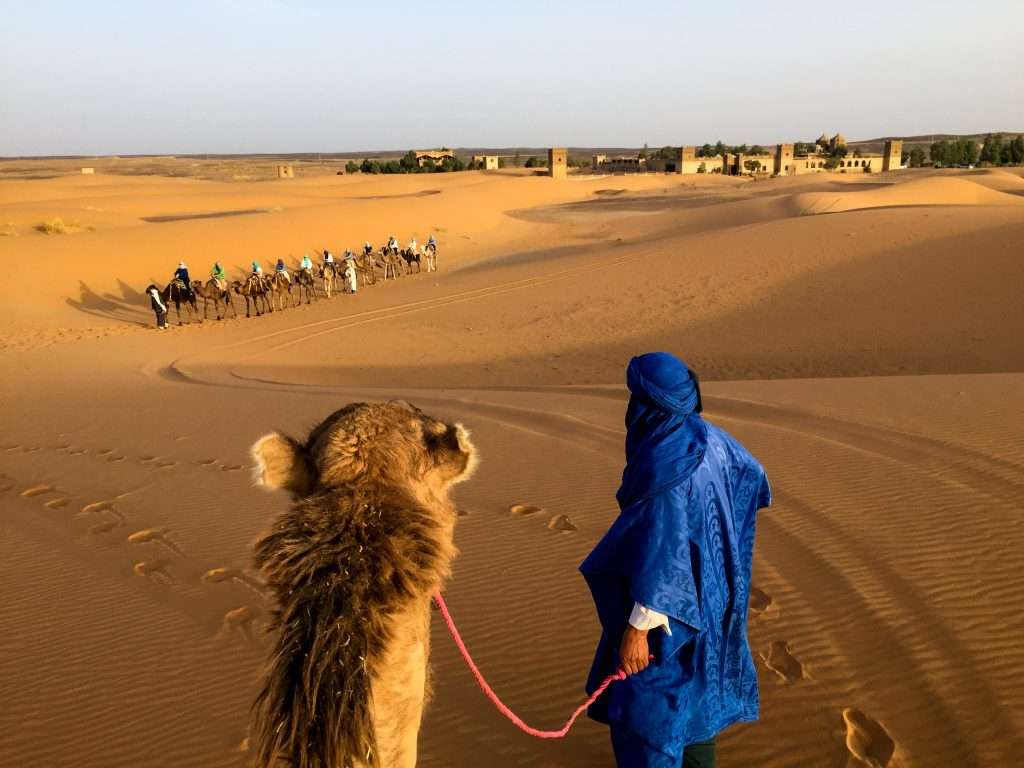 Touareg man in blue with camel and group in distance in Sahara desert near Merzouga, Morocco by Ralph Velasco