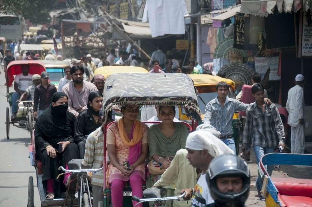 Women laughing on rickshaw in traffic in Delhi, India by Ralph Velasco