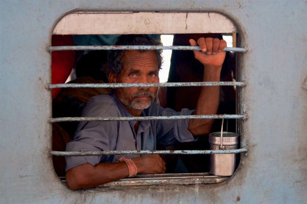Man on Train with Food Tin at Delhi Train Station in India by Ralph Velasco