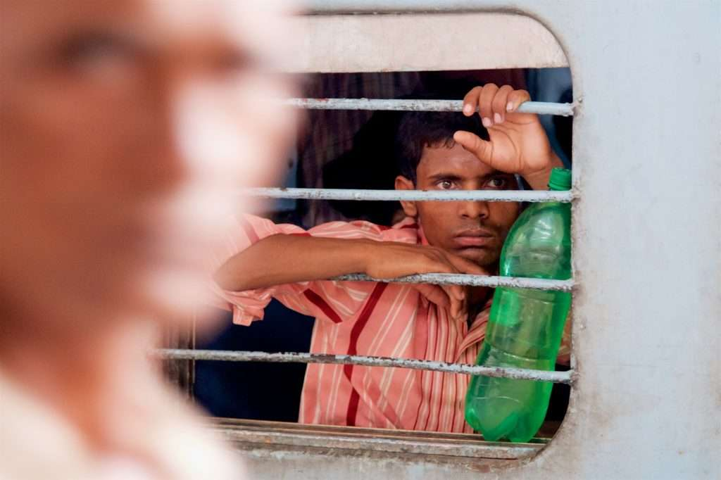 Man with Green Water Bottle on Train at Delhi Train Station in India by Ralph Velasco