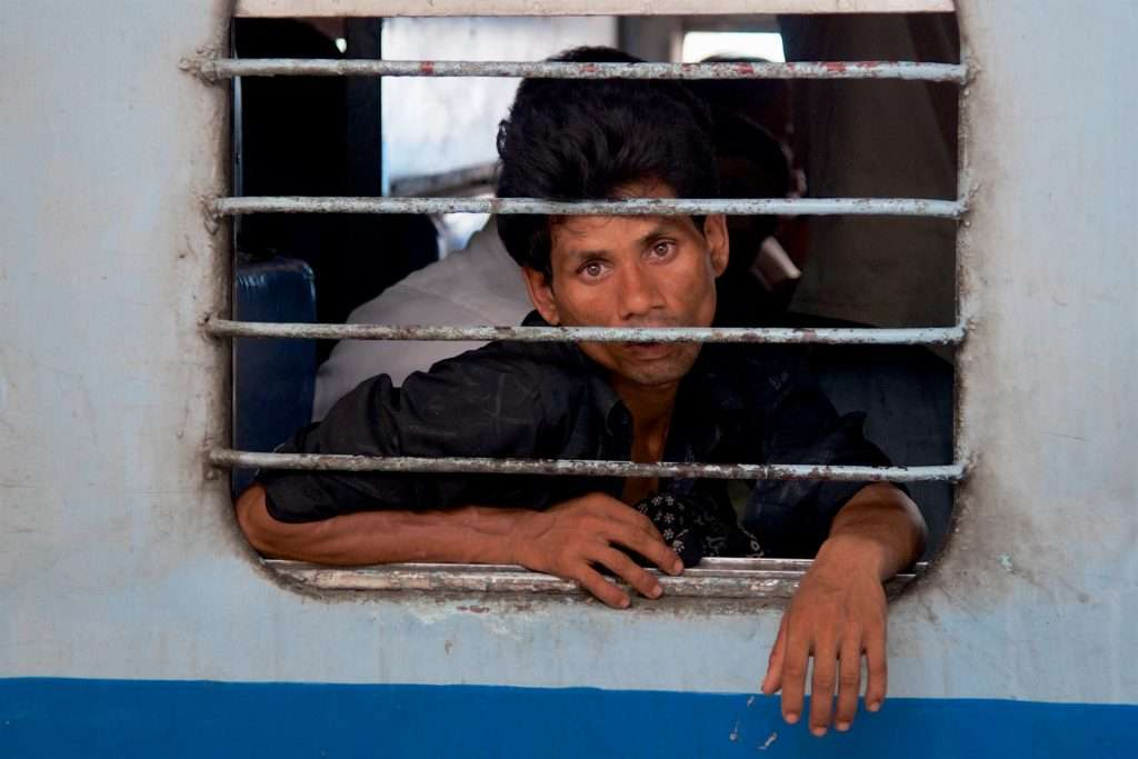 Sad Looking Man on Train at Delhi Train Station in India by Ralph Velasco