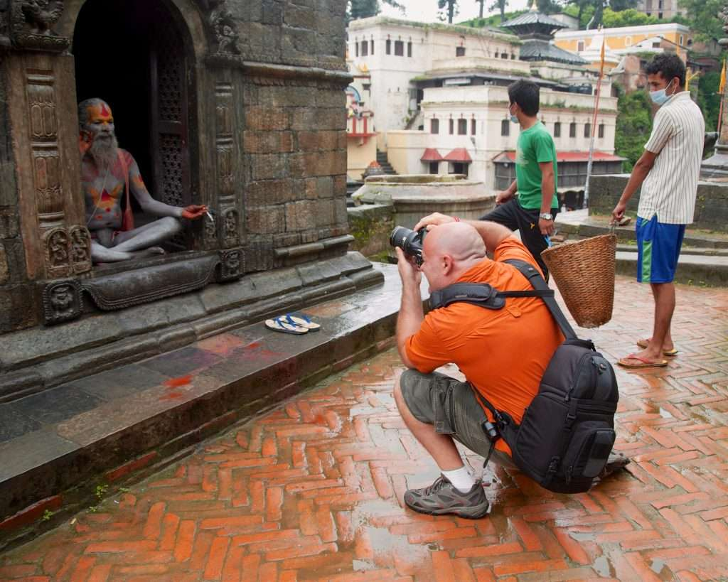 Ralph Velasco photographing sadhu in temple doorway in Pashupatinath, Nepal by Rebecca Foreman