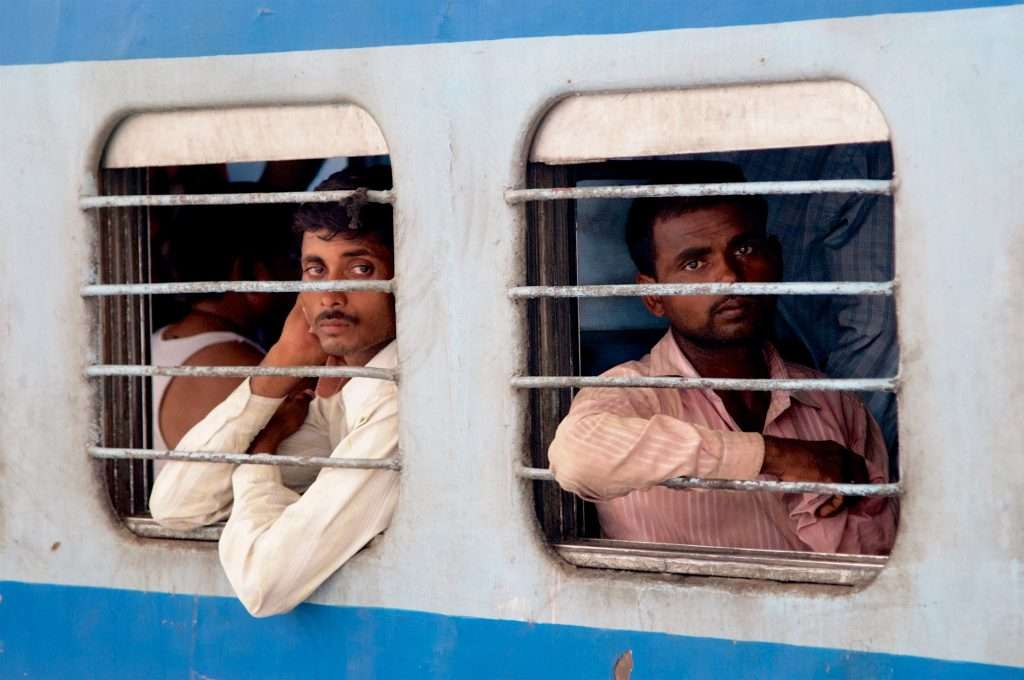 Two Men on Train at Delhi Train Station in India by Ralph Velasco